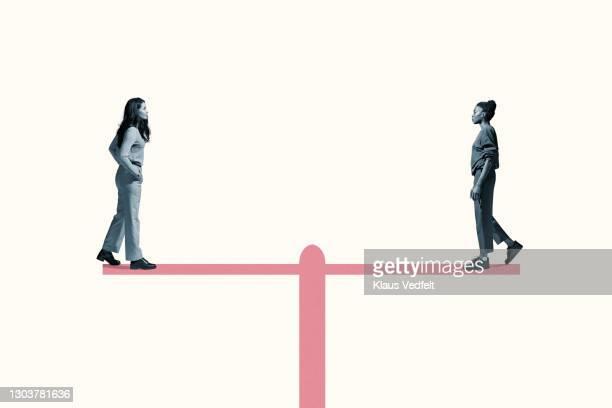 young women standing on equal-arm balance - igualdade - fotografias e filmes do acervo