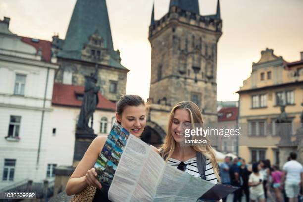 Young women standing on the Charles Bridge and exploring the city with city map