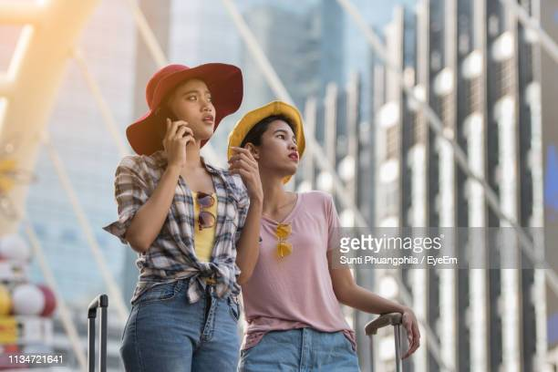 young women standing with luggage on footbridge - man made structure stock pictures, royalty-free photos & images