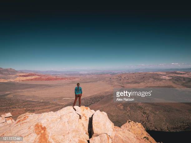a young women stands atop juniper peak in red rocks canyon state park, nevada - nevada stock pictures, royalty-free photos & images