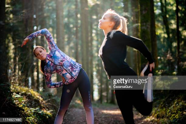 young women stretching before running in forest - long sleeved stock pictures, royalty-free photos & images