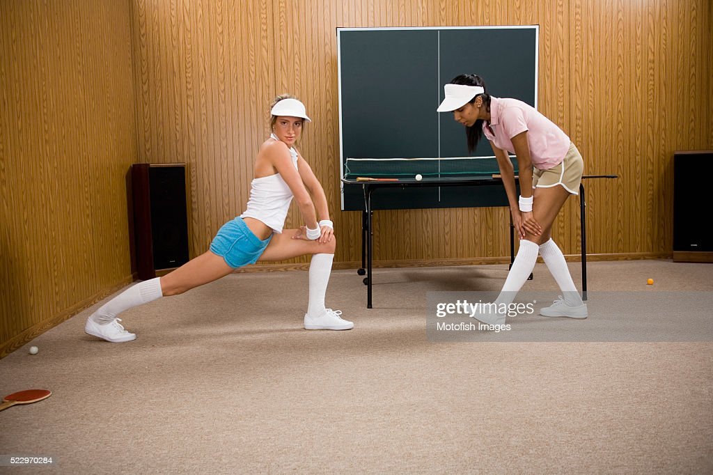 Young Women Stretching by Table Tennis Table : Stock Photo
