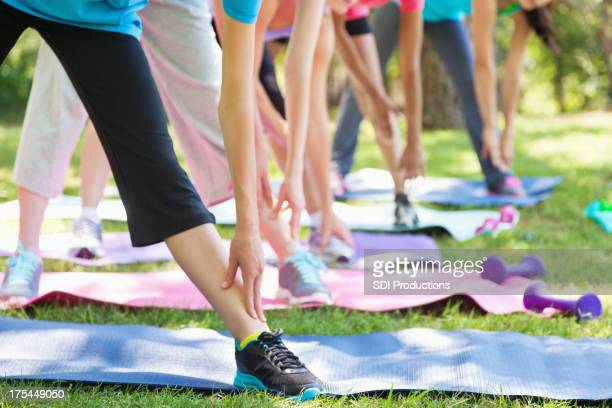 Young women stretching legs during outdoor fitness class