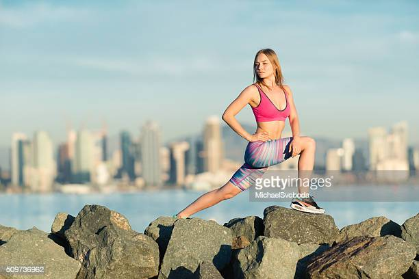 Young Women Stretching With San Diego City Skyline Behind