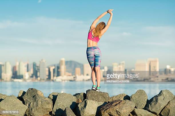 young women stretching with san diego city skyline behind - women wearing spandex stock photos and pictures