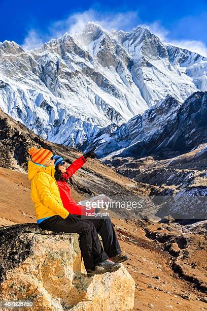 young women studying map in himalayas, lhotse on background - solu khumbu stock pictures, royalty-free photos & images