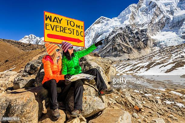 Young women studying map next to signpost, Nepali Himalaya