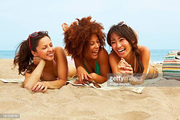 young women sunbathing on beach - women sunbathing stock photos and pictures