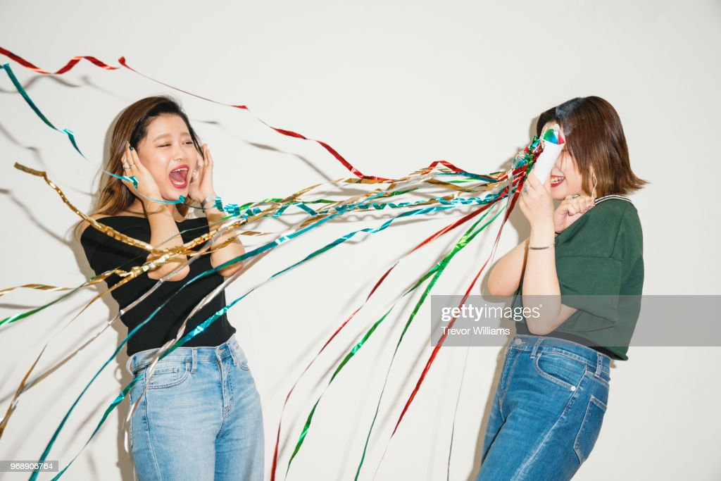 Young women surprising her friend with a party cracker : Stock-Foto