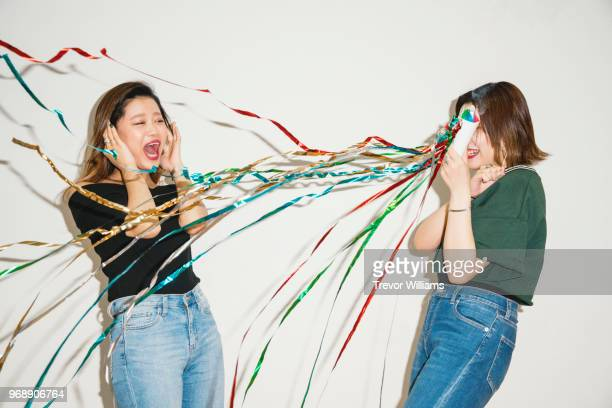 Young women surprising her friend with a party cracker