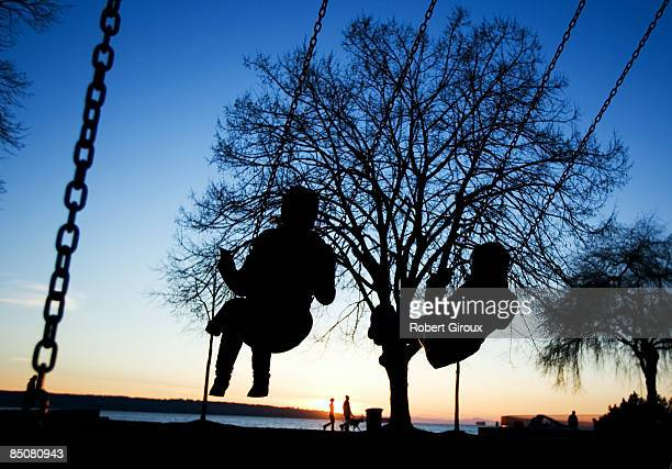 Young women swing and watch the sunset from Stanley Park February 19 2009 in Vancouver British Columbia Canada Vancouver is the host city for the...