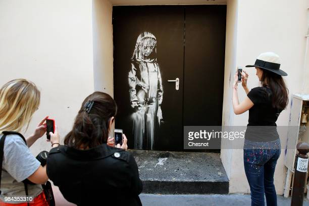 Young women take a picture of a recent artwork attributed to street artist Banksy on June 26 2018 in Paris France Yesterday a new artwork attributed...