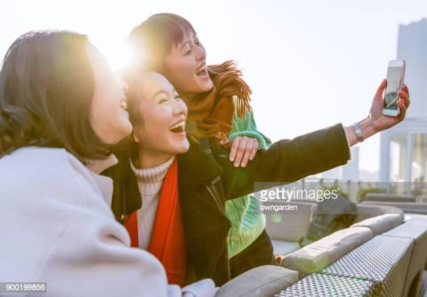 jovens mulheres tomam selfies com seus telefones celulares - china oriental - fotografias e filmes do acervo