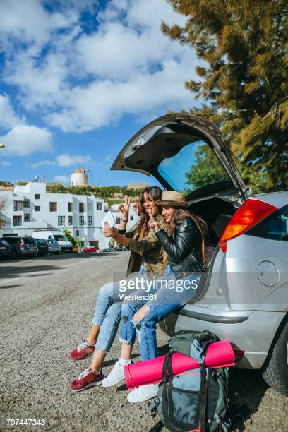 Young women taking a selfie sitting in the trunk of a car.