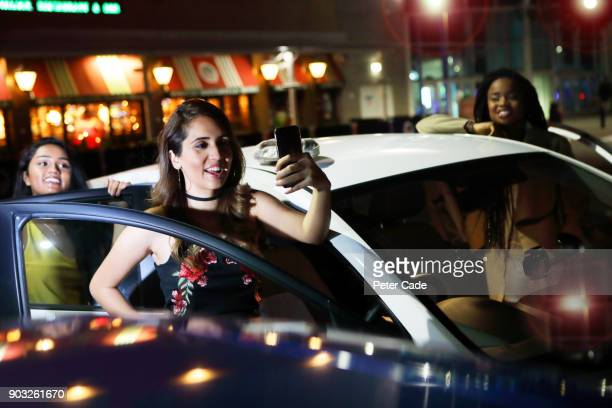 Young women taking photo of themselves stood by car on night out