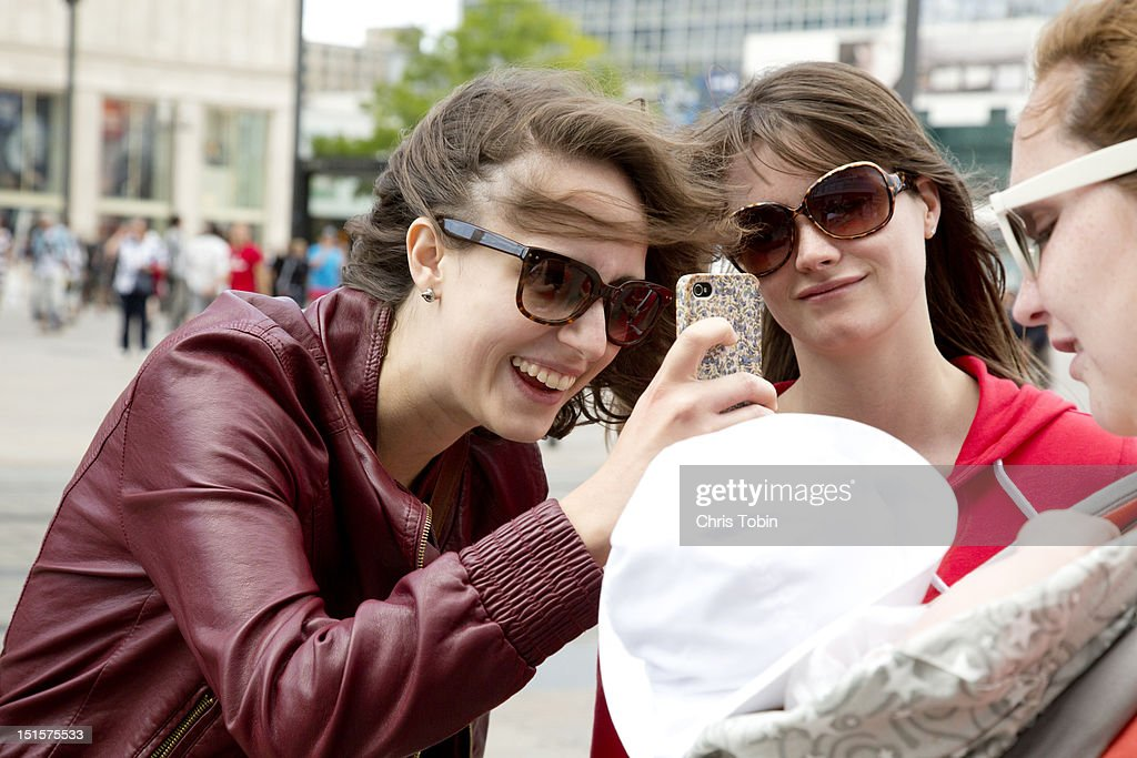 Young women taking photo with cell phone : Stock Photo