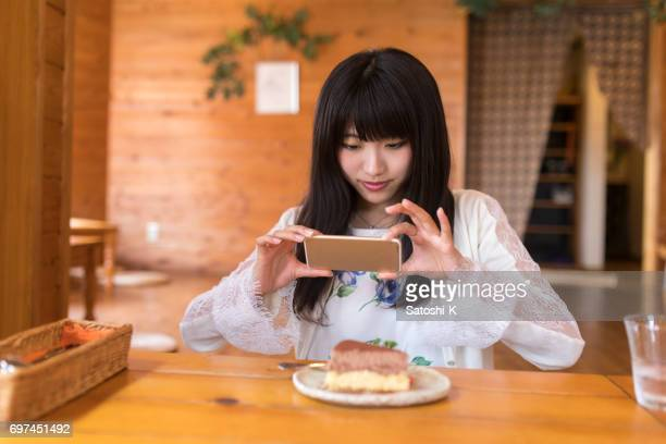 young women taking pictures of cake, in wooden log cabin restaurant - capturing an image stock pictures, royalty-free photos & images