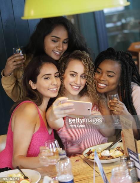 young women taking selfie in restaurant - cuatro personas fotografías e imágenes de stock