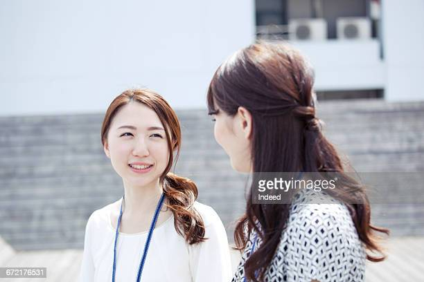 Young women talking face to face