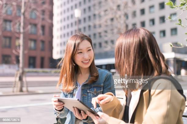 若い女性のデジタル タブレットを使用して市の話 - 30 34歳 ストックフォトと画像