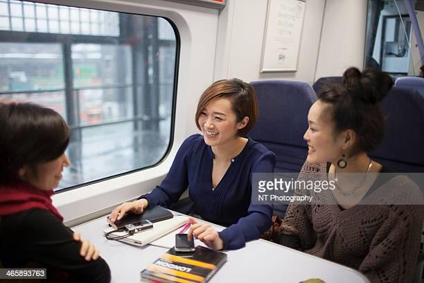 Young women talking on train