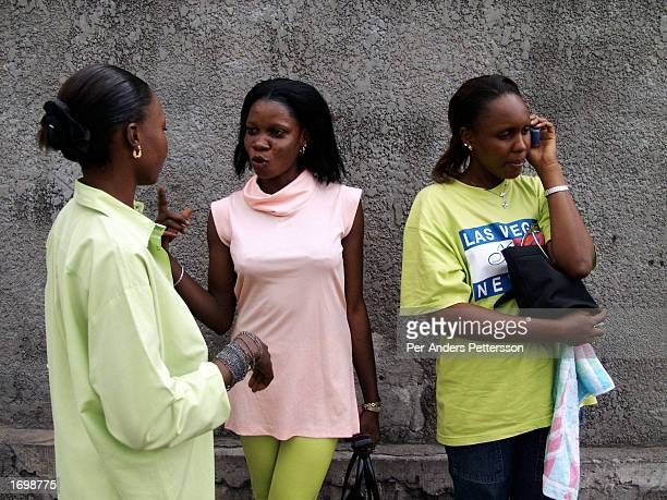 A young women talks on a mobile phone after a church service while her friends are chatting on February 28 2002 in Lingwala district in Kinshasa...