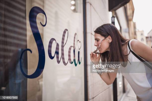 young women tourist discovering italy, looking at store window - saldi foto e immagini stock