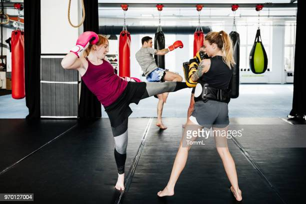 young women training together at kickboxing gym - muay thai stock pictures, royalty-free photos & images