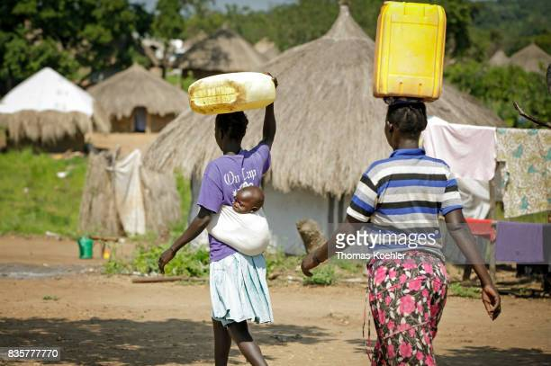 Young women transport canisters with water on their head One of them is carrying a child in a handkerchief on her back Daily life at the Rhino...