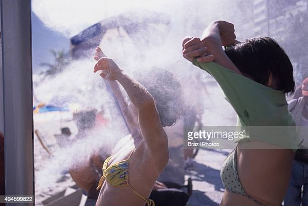 Young women use the refreshing machines installed at Ipanema beach Rio de Janeiro Brazil on a hot day cool water drops