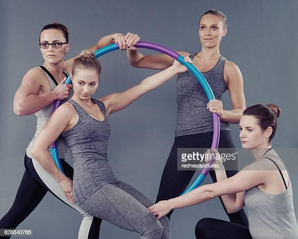 Young women using hula hoop, grey background