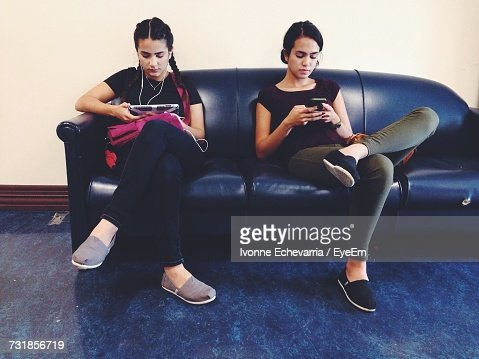 Young Women Using Mobile Phone While Sitting On Sofa