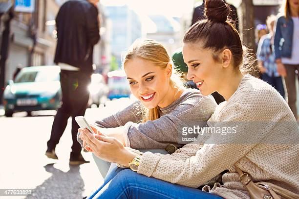 Mujeres jóvenes mediante teléfono inteligente