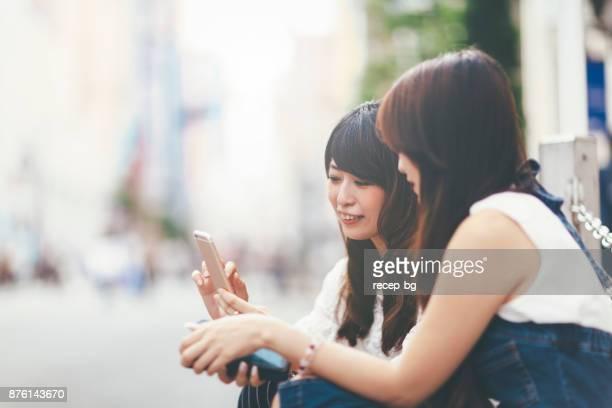 若い女性がスマートフォンを使用して - スマートフォン ストックフォトと画像