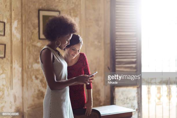 Young women using smart phone while standing at home