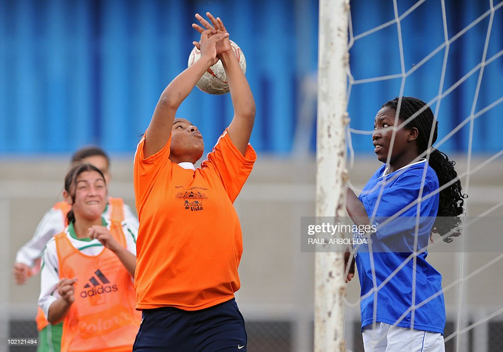 Young women vie for the ball during the 'Mundialito' football tournament in Medellin, Antioquia department, Colombia on June 15, 2010. The 'Mundialito' tournament takes place every four years with the participation of Medellin soccer schools. AFP PHOTO/Raul ARBOLEDA