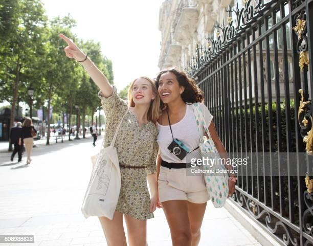 2 young women visiting paris - touriste photos et images de collection