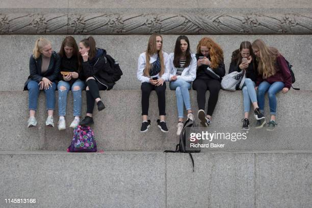 Young women visitors to the capital sit beneath Nelson's Column with a view across Trafalgar Square and look at their mobile phones on 20th May 2019...