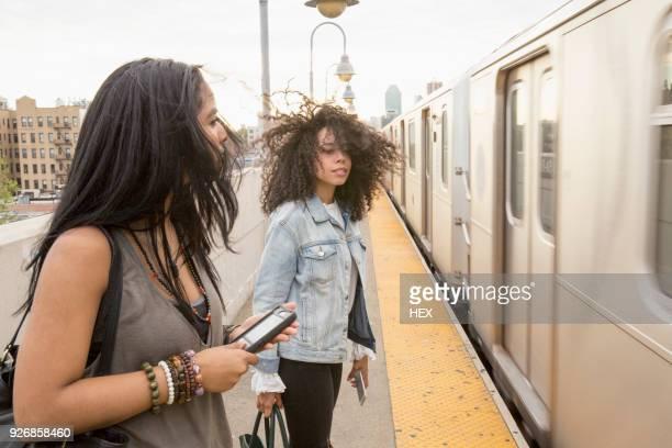 young women waiting at a train station in queens, new york - queens stock-fotos und bilder