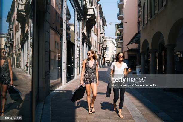 young women walk down shopping street - playsuit stock pictures, royalty-free photos & images