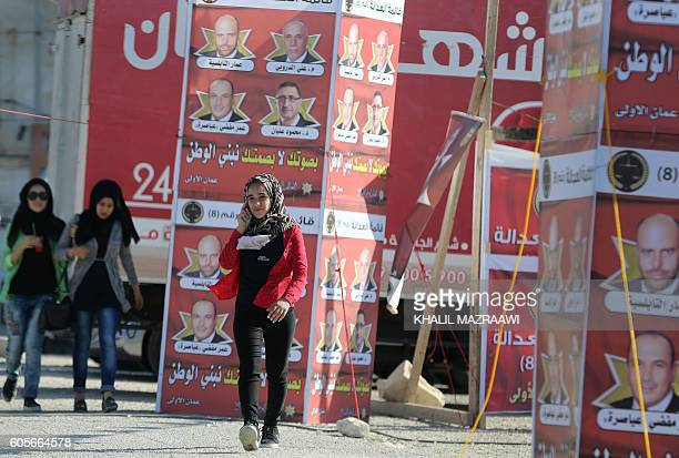 Young women walk past election campaign posters in the Jordanian capital Amman on September 14 2016 ahead of the general elections to be held on...
