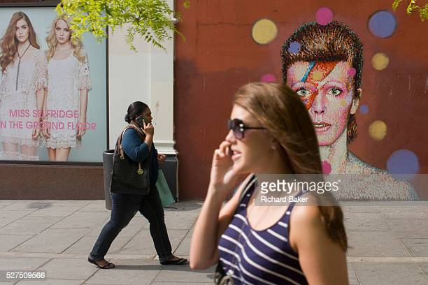 Young women walk past the mural of iconic musician and singer David Bowie has appeared on the wall of Morleys department store in Brixton Lambeth...