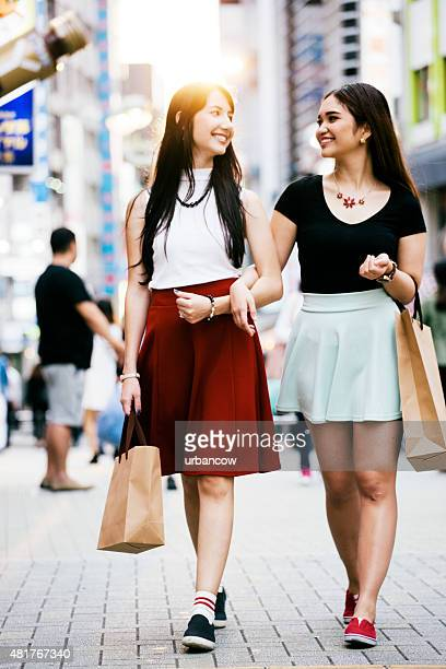 Young women walk together, smiling and laughing, shopping district, Tokyo