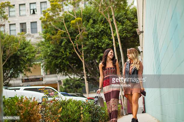young women walking along pavement - maxi dress stock pictures, royalty-free photos & images