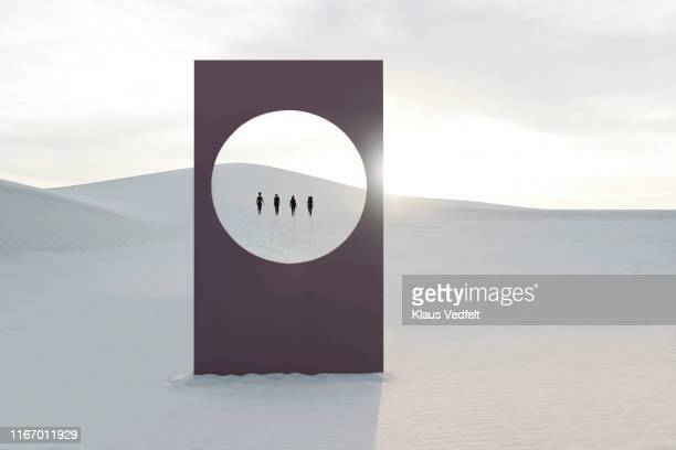 Young women walking at white desert seen through window frame
