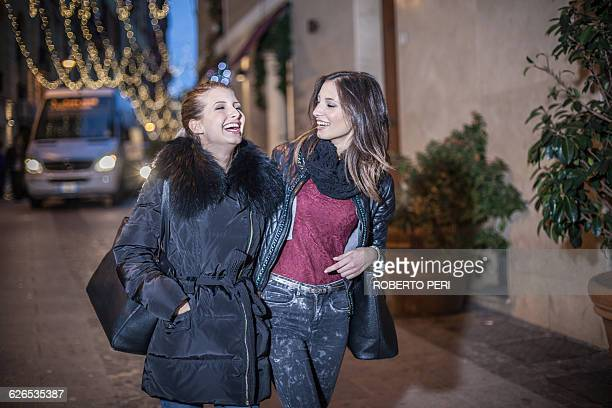 Young women walking down street in the evening arm in arm laughing