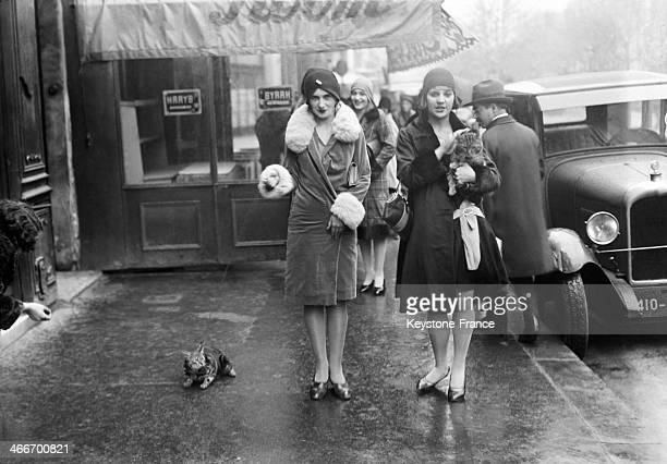 Young women walking their cat in November 1929 in Paris France