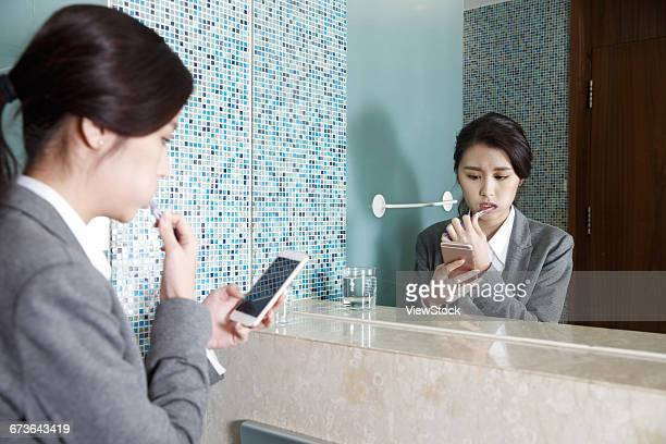 Young women watch phone while brushing her teeth