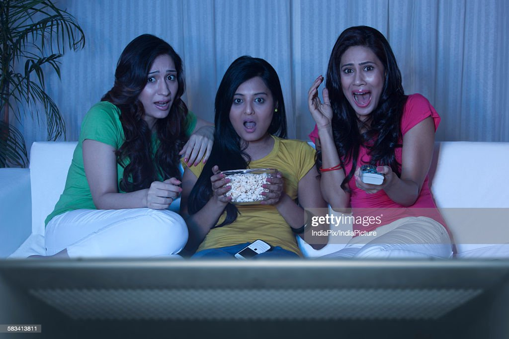 Young women watching a horror movie : Stock Photo