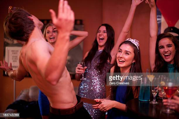 Young women watching male stripper at hen party